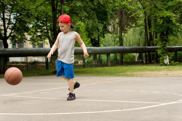 バスケットボールをするスポーティな男の子
