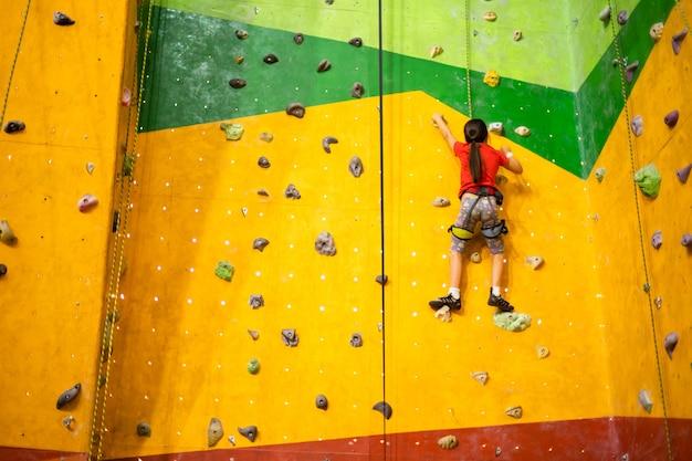 ジムの実用的な壁に人工岩を登るスポーティな女の子