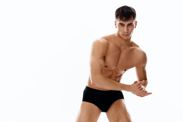 Sporty macho man in dark shorts light background