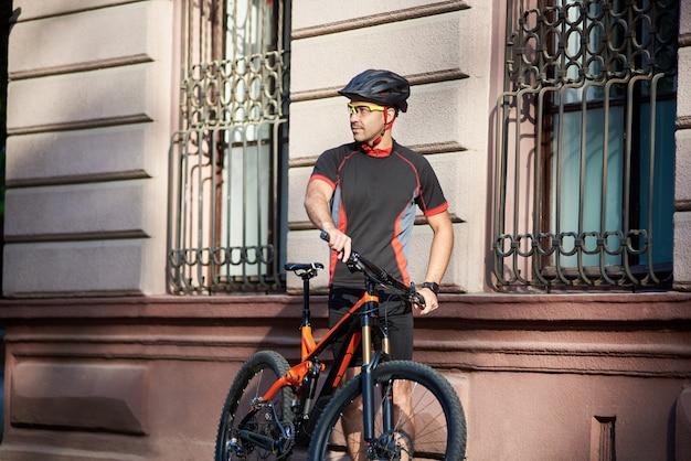 Sporty мужской велосипедист стоя около старого исторического здания рядом с велосипедом смотря далеко и отдыхая.