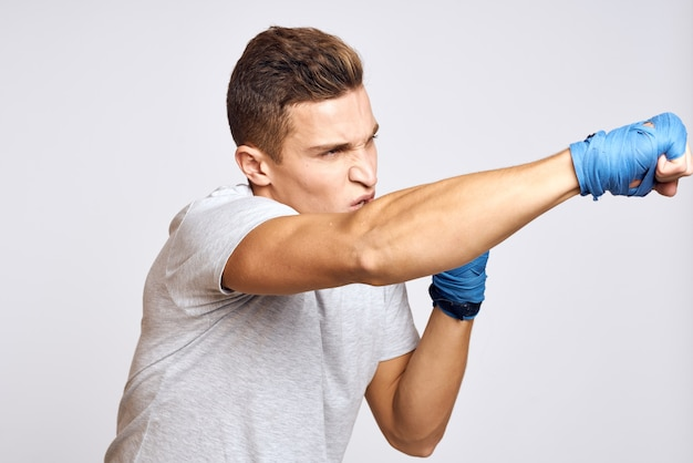 Sporty male boxer in blue gloves practicing punches on a light background. cropped view.