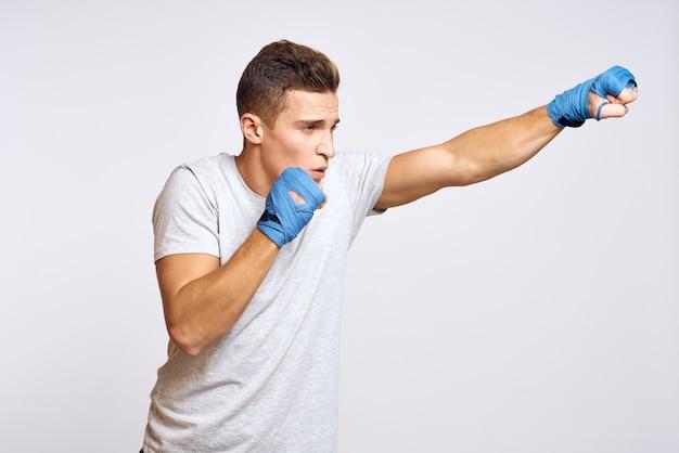 밝은 배경에 펀치를 연습하는 파란색 장갑에 스포티 한 남성 권투 선수보기를 잘립니다. 고품질 사진