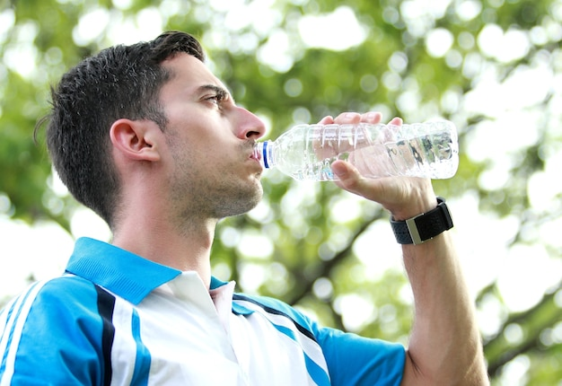 Sporty male runner drinking mineral water at the break after running
