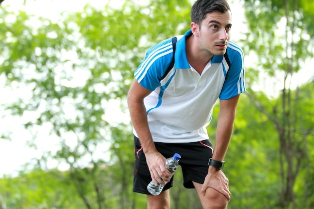 Sporty male runner taking a break after tired running while holding a bottle of mineral water Premium Photo