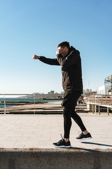 Sporty man 20s in black tracksuit boxing and doing punch during morning workout by seaside