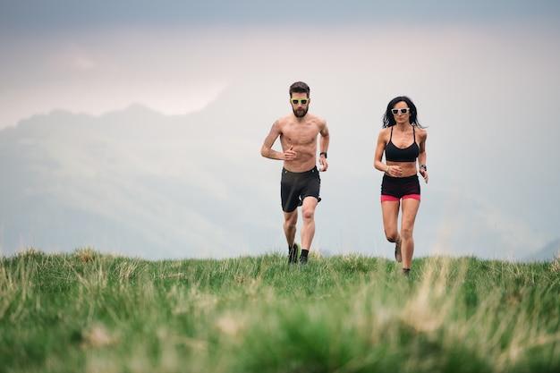 스포티 한 남자와 여자는 언덕 초원에서 여름에 뜨거운 실행