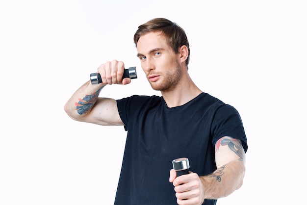Sporty man in a black t-shirt with dumbbells in his hands on a white background