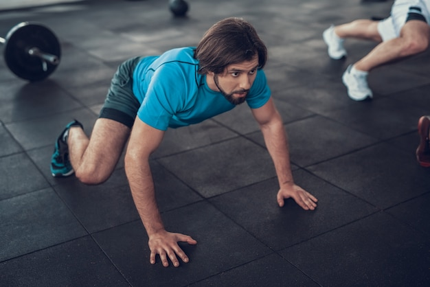 Sporty man in blue t shirt crawls on gym floor.