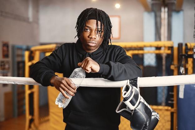 Uomo sportivo boxe. foto del pugile su un anello. uomo afroamericano con bottiglia d'acqua.