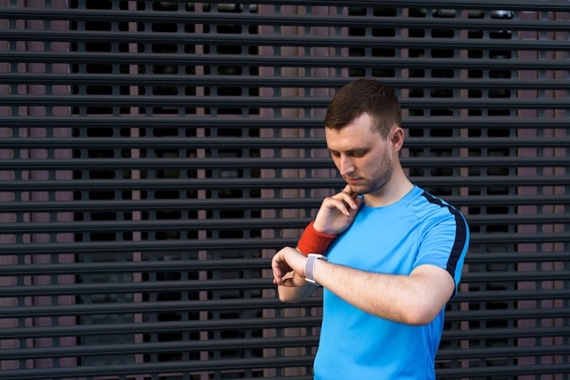 Sporty man checks his pulse during city workout