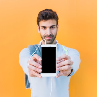 Sporty man demonstrated smartphone