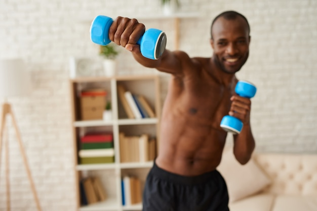 Sporty man doing boxing exercises with dumbbells.