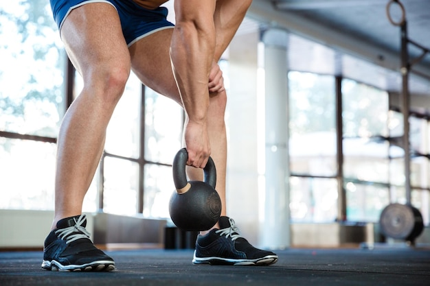 Sporty man hands and legs lifting kettle ball