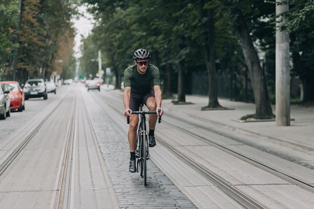Sporty man in helmet and glasses riding bike on street