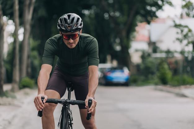 Sporty man in helmet practising in cycling on street