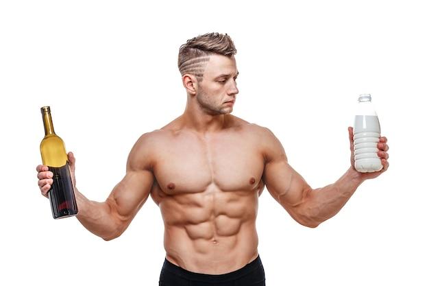 와인과 우유를 들고 스포티 한 남자는 선택, 건강한 라이프 스타일 또는 알코올에 직면 해 있습니다. 건강, 스포츠, 선택, 건강 식품 및 건강한 라이프 스타일 개념.