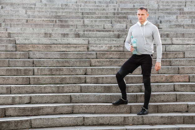 Sporty man holding a bottle of water on stairs