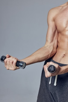 Sporty man holding dumbbells in hands biceps workout exercise fitness. high quality photo