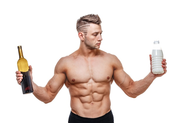 Sporty man holding a wine and milk and faces a choice, healthy lifestyle or alcohol. health, sports, choice, healthy food and healthy lifestyle concept.