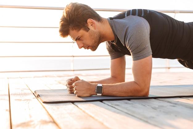 운동복에 스포티 한 남자가 매트에 누워 아침에 해변에서 목재 부두에서 운동하는 동안 판자를하고