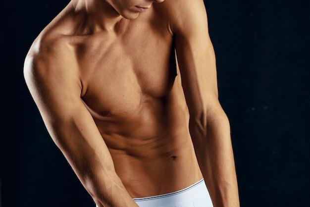 흰색 반바지에 스포티 한 남자 몸통 운동 자른 보기 스튜디오를 펌핑