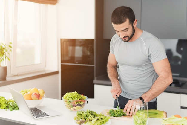 A sporty man is preparing a salad in the kitchen.