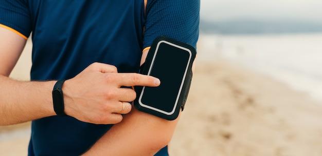 スポーティな男性が腕章の携帯電話を使用しています。