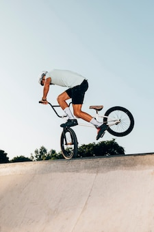 Sporty man jumping high with bicycle