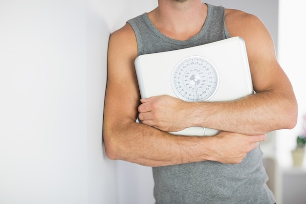 Sporty man leaning against wall holding a scale