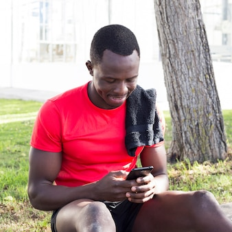 Sporty man in park looking at smartphone