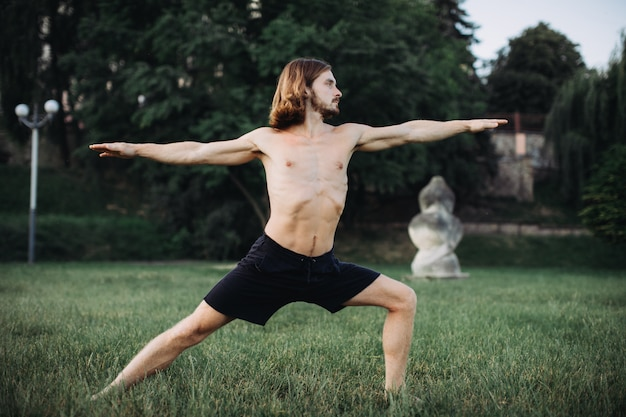 Sporty man practicing yoga outdoor