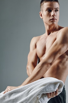 Sporty man pumped up body workout bodybuilders towels in hands