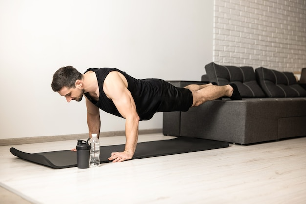 Sporty man pushing from floor with legs on sofa. workout on black yoga mat. man in black sportswear exercising at home. white modern room on background. strong man excercising to have a fit body.