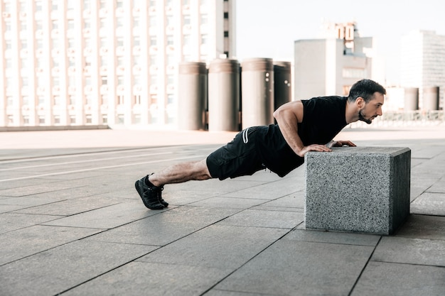 Sporty man pushing from stone cube with legs on asphalt. workout outdoors. man in black sportswear exercising at morning. strong man excercising to have a fit body. fitness. city on background.