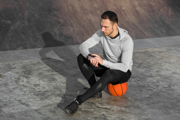 Sporty man resting on a basketball