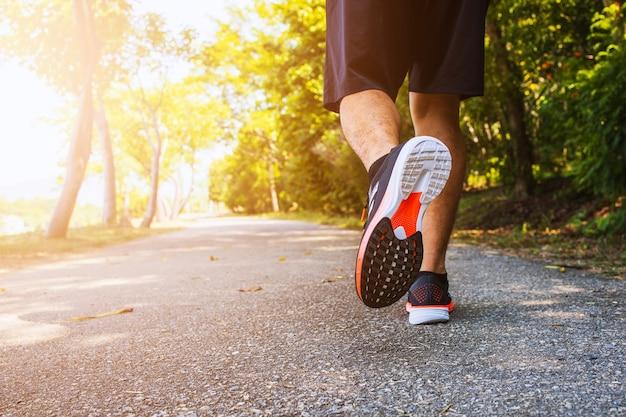 Спортивный мужчина-бегун бежит по дорогам в парке с мягким фокусом на заднем плане