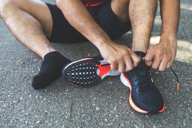 Бегун спортивного человека, бегущий по дорогам в парке
