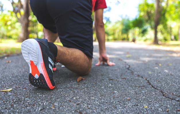 公園内の道路を走っているスポーティな男性ランナー