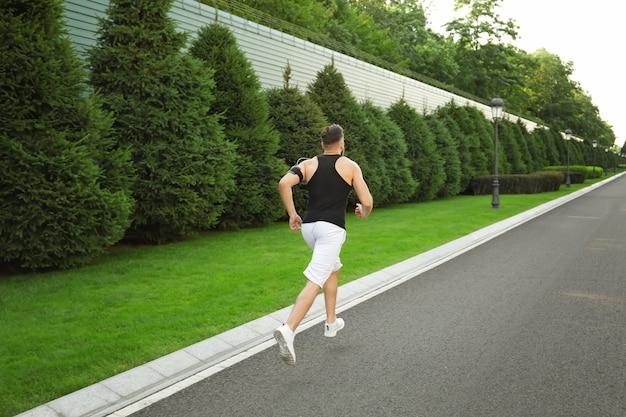 屋外で走るスポーティな男