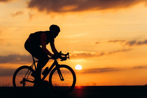 Sporty man in silhouette riding bike on paved road