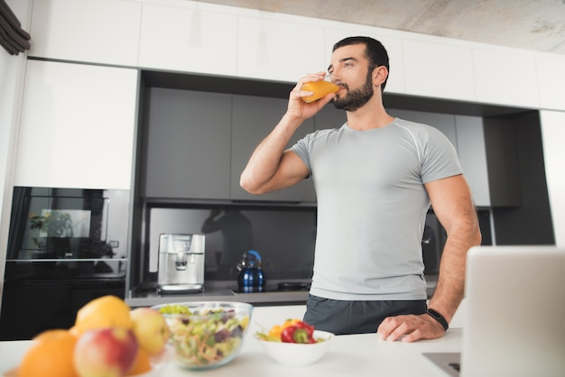 A sporty man stands in the kitchen and drinks orange juice.