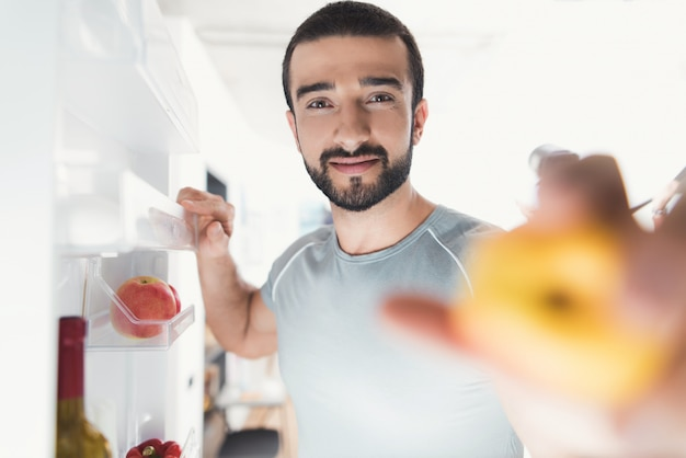 Sporty man stands in kitchen and takes fresh vegetables.