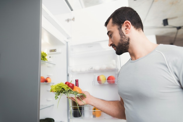 A sporty man stands in the kitchen and takes fresh.