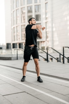 Sporty man stretching arms before jogging. runner in black sportswear excercising at morning. healthy lifestyle concept. morning city on background. active living. outdoor fitness.