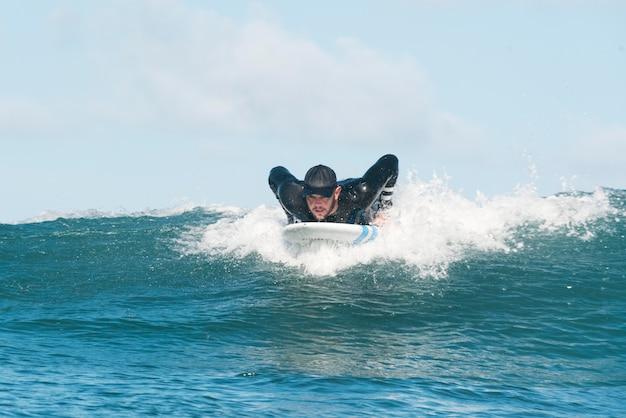 Uomo sportivo che fa surf alle hawaii