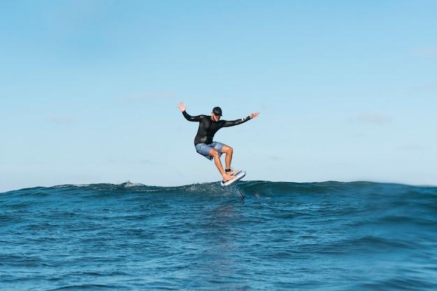 ハワイでサーフィンするスポーティな男 無料写真