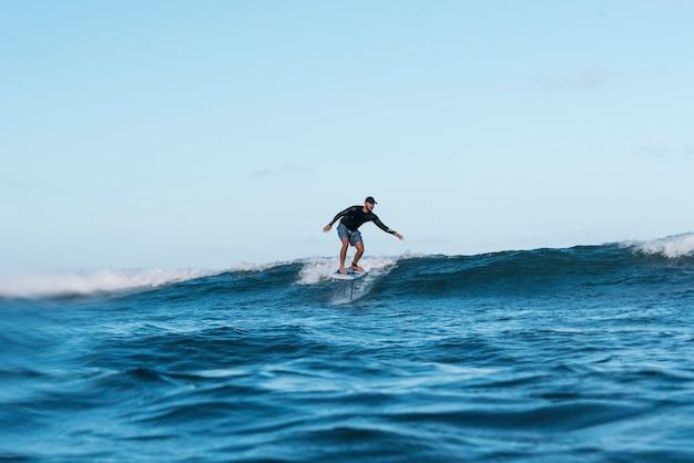 ハワイでサーフィンするスポーティな男