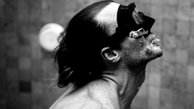 プールのマスクで泳ぐスポーティな男