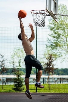 Sporty man throwing ball to hoop