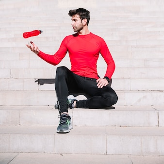 Sporty man throwing bottle up